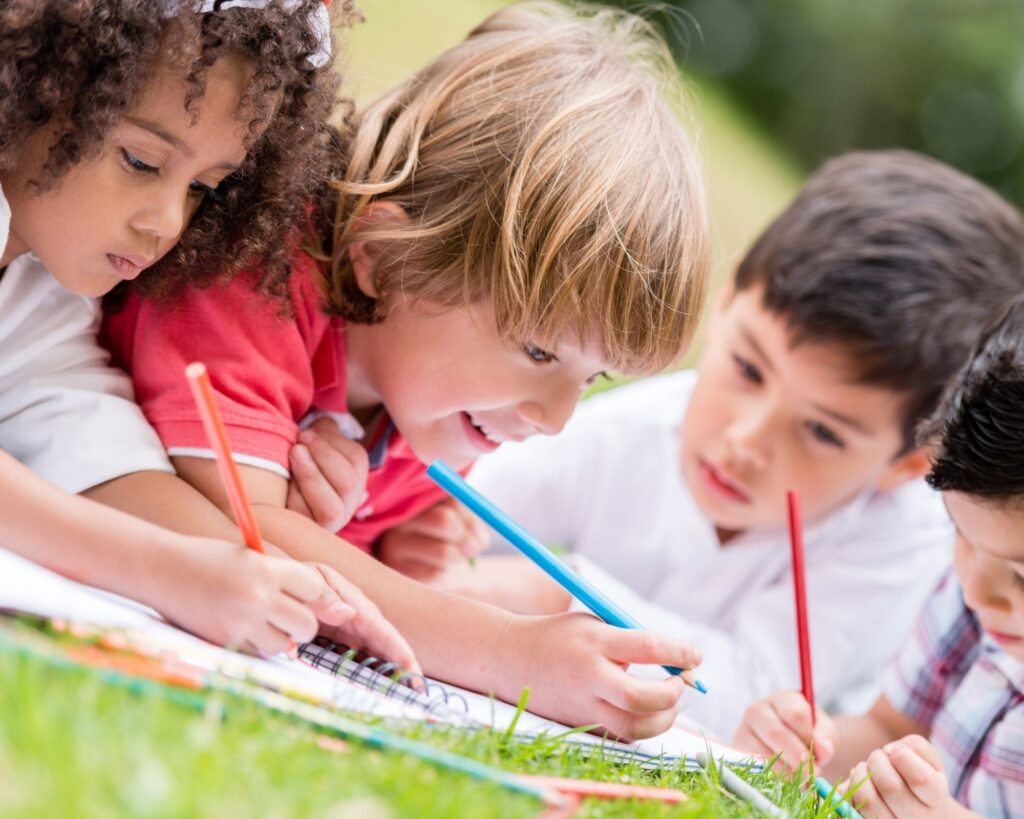 kids coloring in the grass